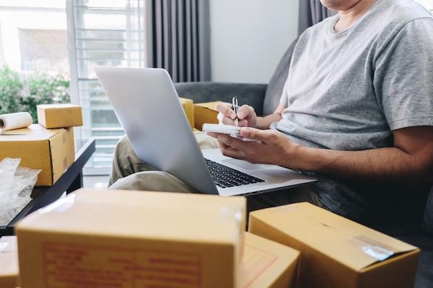 Il giovane freelance della pmi dell'imprenditore che lavora con l'imballaggio d'imballaggio della nota ordina il mercato online di consegna