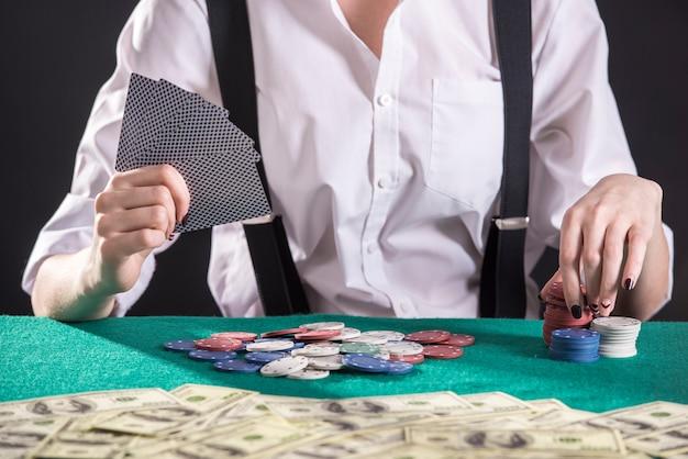 Il giovane gangster femminile gioca a poker nel casinò.