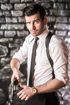Il giovane gangster fiducioso estrae il revolver dalla fondina.