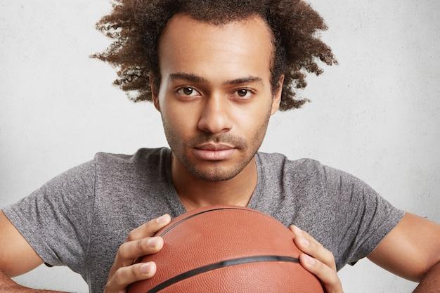 Il giovane giocatore di basket nero tiene la palla, guarda con sicurezza,
