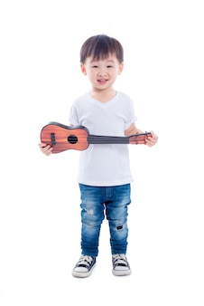 Il giovane giocattolo asiatico della chitarra della tenuta del ragazzo e sorride sopra fondo bianco