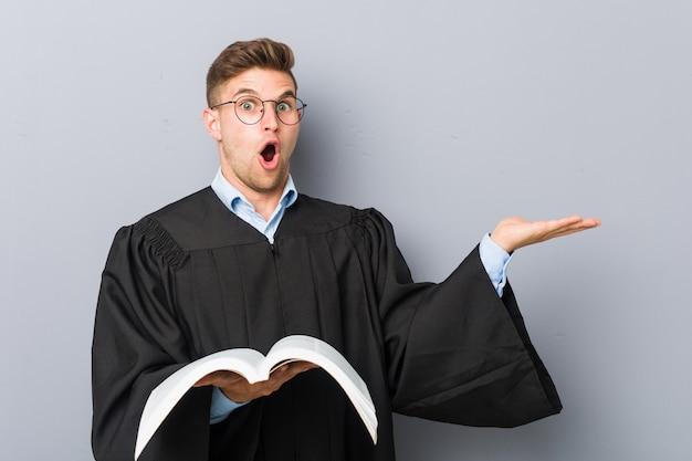Il giovane giurista che tiene un libro ha impressionato tenendo la palma del copyspace.
