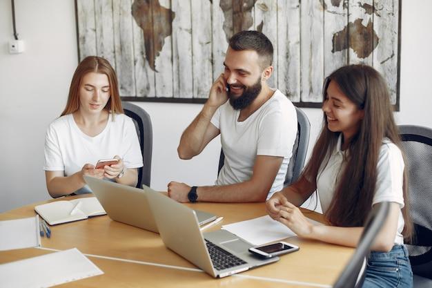 Il giovane gruppo che lavora insieme e usa il computer portatile