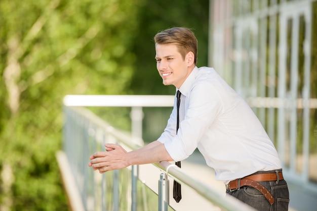 Il giovane ha vestito il riposo convenzionale al balcone dell'ufficio.