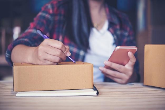 Il giovane imprenditore, proprietario di affari dell'adolescente lavora a casa, scatola per la consegna