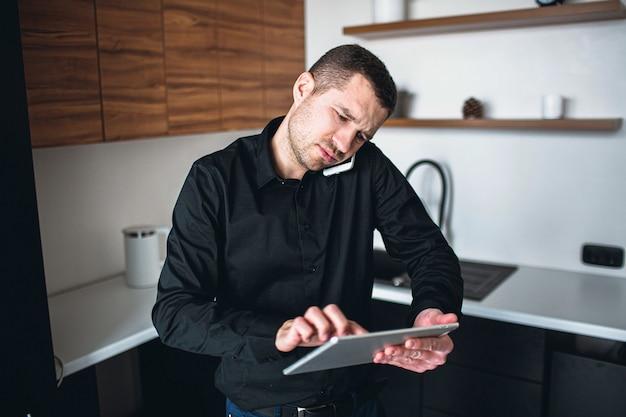 Il giovane imprenditore serio impegnato ha una telefonata e usa il tablet per il lavoro remoto. l'uomo sta in cucina da solo. il ceo di un uomo d'affari o di un'azienda ha i suoi affari.