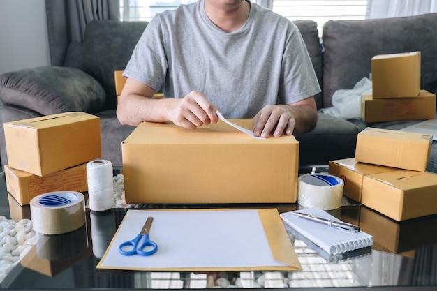 Il giovane imprenditore uomo delle pmi riceve il cliente dell'ordine e lavora con il mercato online di consegna della scatola di materiali di imballaggio