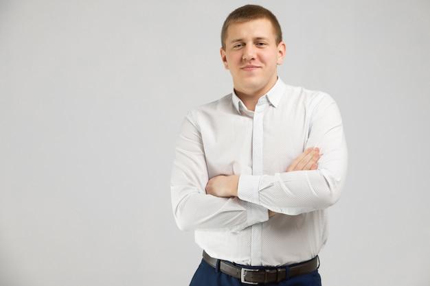 Il giovane in camicia bianca sta isolato su fondo bianco con le armi piegate sul petto