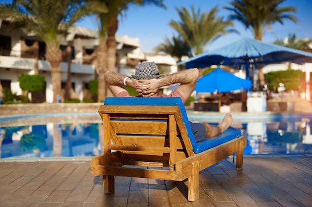 Il giovane in cappello si trova su louger vicino alla piscina per rilassarsi concetto di vacanza estiva.