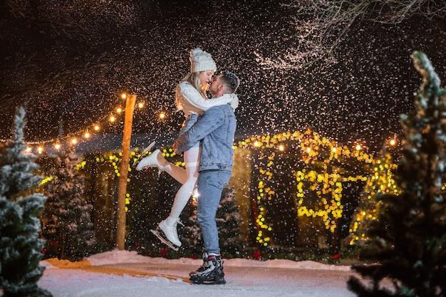 Il giovane in jeans copre la tenuta della donna bionda abbastanza giovane sulla pista di pattinaggio sul ghiaccio.