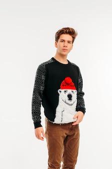 Il giovane in maglione accogliente orso su sfondo bianco