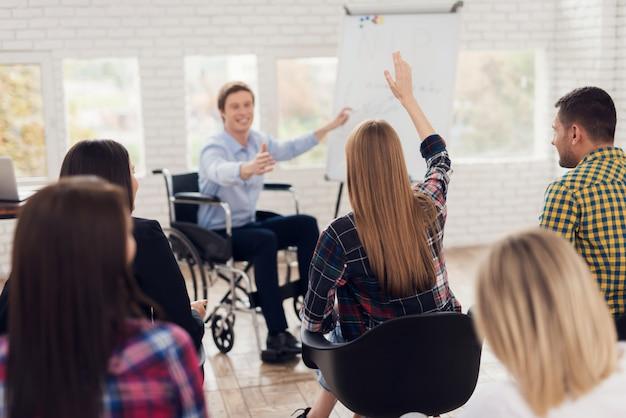Il giovane in sedia a rotelle sta indicando a flipchart