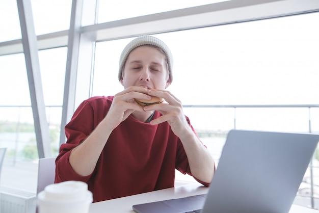 Il giovane in un abito casual si siede con un quaderno in un ristorante fast-food e mangia un hamburger