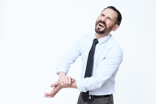 Il giovane in un vestito tiene una mano irritata