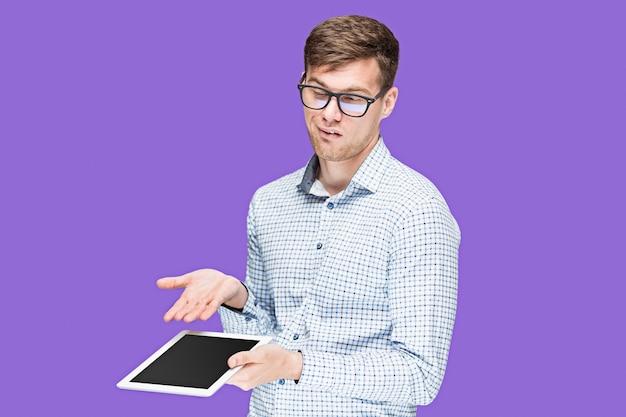 Il giovane in una camicia che lavora al computer portatile su sfondo lilla