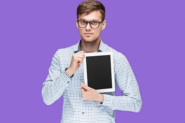 Il giovane in una camicia che lavora al computer portatile sulla parete lilla