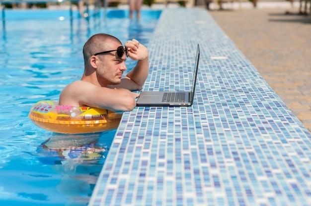 Il giovane in vacanza estiva con il portatile, business online. distanza ufficio a casa in piscina in anello di gomma in quarantena