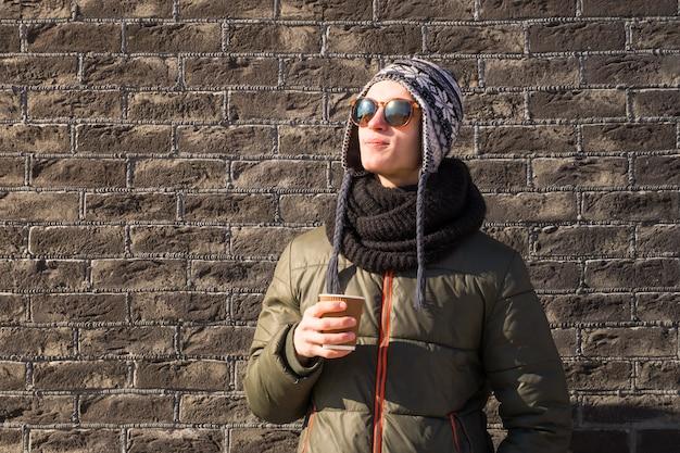 Il giovane in vestiti dell'inverno tiene la tazza di caffè