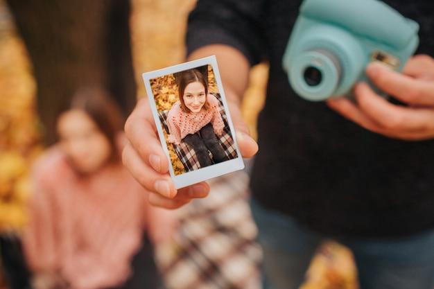 Il giovane in vestiti neri mostra l'immagine in una mano e la macchina fotografica in un'altra. ci sono giovani donne sulla foto. si siede su una coperta oltre a lui.