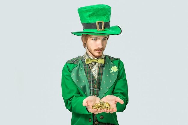 Il giovane in vestito verde tiene le monete dorate in mani. sembra seriamente. il ragazzo indossa l'abito di san patrizio. isolato su grigio