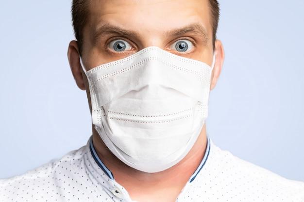 Il giovane indossa maschere per prevenire l'inquinamento atmosferico, la foschia e l'inquinamento da polvere e fumo pm 2.5 su bianco. protezione medica contro le malattie trasportate dall'aria, coronavirus. l'uomo ha paura di contrarre l'influenza
