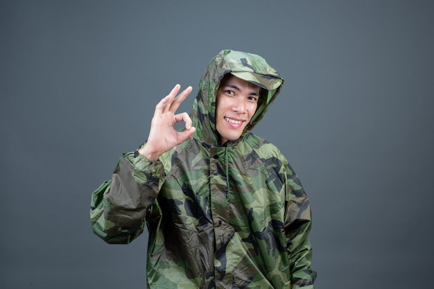 Il giovane indossa un impermeabile mimetico e mostra gesti diversi.