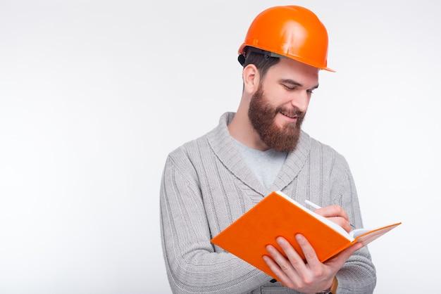 Il giovane ingegnere sorridente che porta il cappello duro sta scrivendo qualcosa nel suo quaderno sulla parete bianca