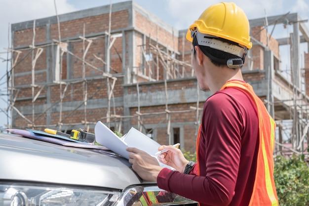 Il giovane ingegnere sta leggendo un progetto davanti a una casa incompiuta.