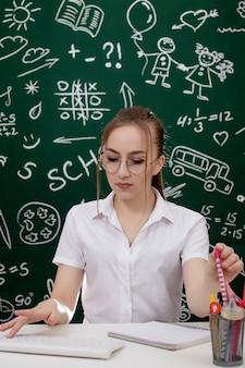 Il giovane insegnante sta sedendosi vicino alla lavagna in aula