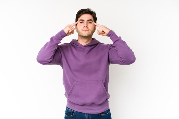 Il giovane isolato su bianco si è concentrato sul compito, mantenendo l'indice che indica la testa.