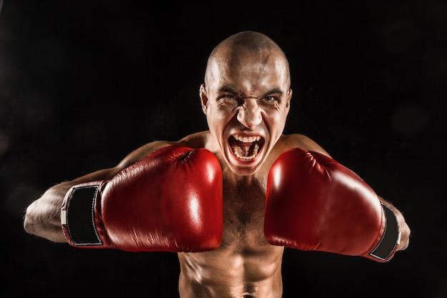 Il giovane kickboxing sul nero con la faccia urlante