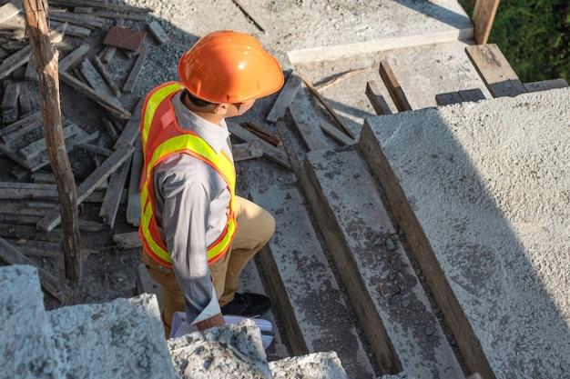 Il giovane lavoratore dell'ingegnere in casco protettivo e la carta dei modelli ispeziona dentro la costruzione al cantiere