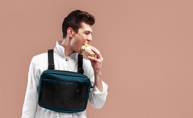 Il giovane lavoratore maschio alla moda con la borsa dell'impianto di perforazione del petto sta mangiando un hamburger succoso saporito su un fondo bianco