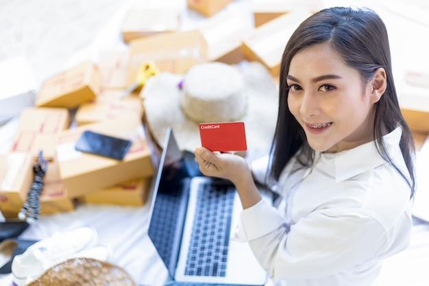 Il giovane lavoro adolescente grazioso a casa scrive la nota sulla cassetta dei pacchi. donne asiatiche felici dopo il nuovo ordine dal cliente, dall'imprenditore online delle pmi dello shopping o dal concetto di lavoro indipendente.