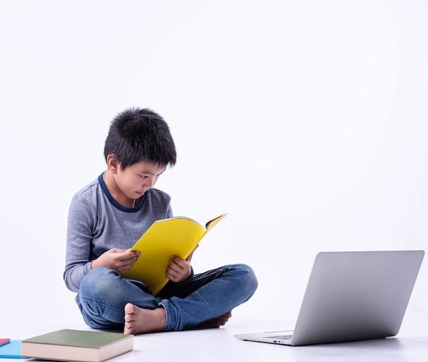Il giovane libro di lettura con sentimento interessato, laptop messo sul lato destro, bambini intelligenti