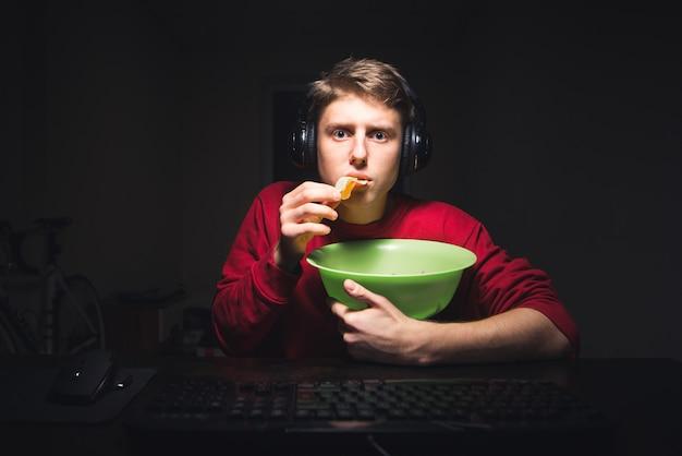 Il giovane mangia patatine a casa guardando un video su internet su un computer