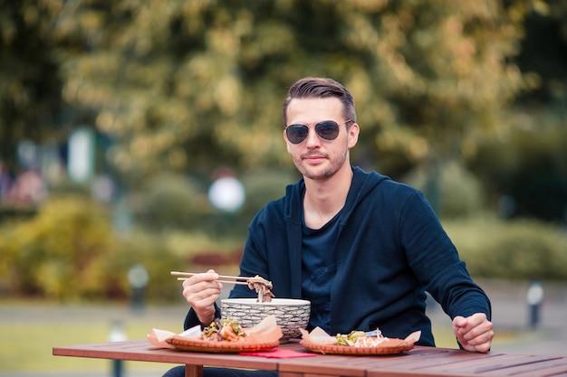 Il giovane mangiatore di uomini porta via le tagliatelle sulla via