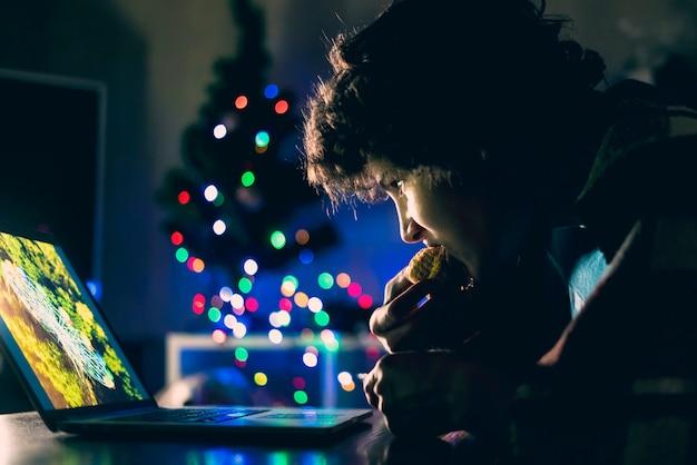 Il giovane maschio che si siede davanti al computer portatile guarda i film e mangia il dolce dolce nella notte a casa f