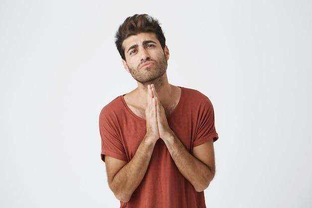 Il giovane maschio italiano attraente in maglietta rossa che tiene i palmi ha premuto insieme lui con le espressioni pentite che si scusano con la fidanzata.