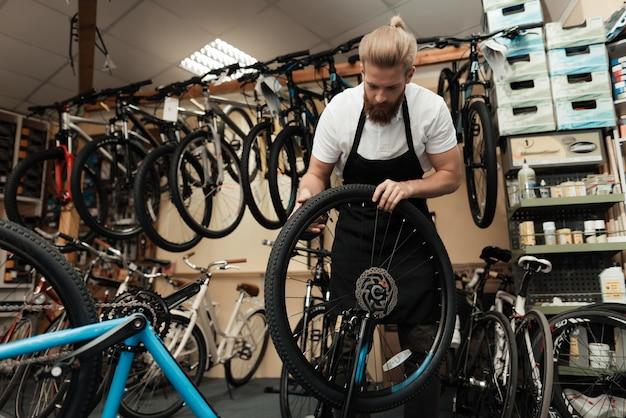 Il giovane meccanico ripara la bicicletta nell'officina della bici.