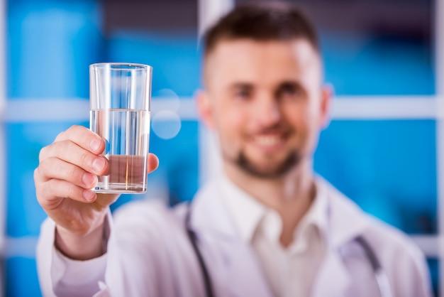 Il giovane medico sta tenendo un bicchiere d'acqua.