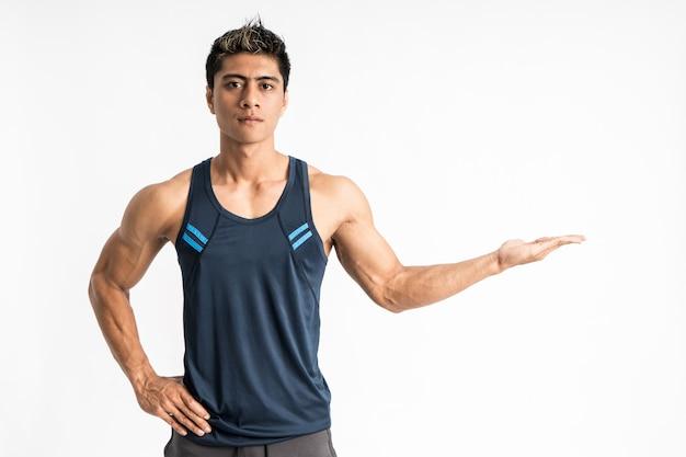 Il giovane muscolare che indossa abbigliamento sportivo sta rivolto in avanti con qualcosa presente sulla sua mano
