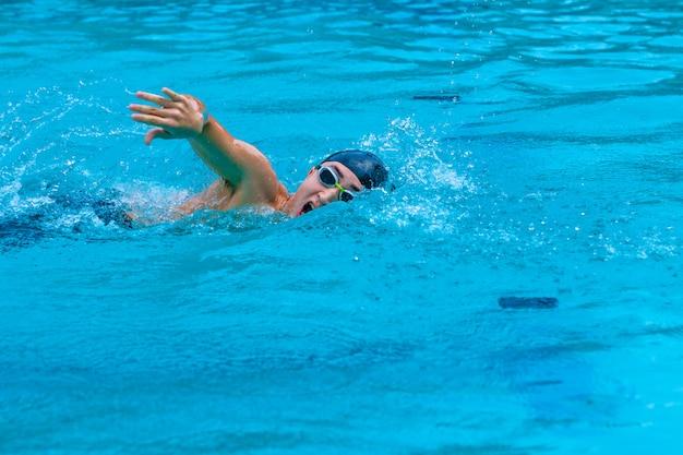 Il giovane nuota il freestyle in una piscina