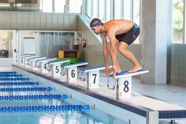 Il giovane nuotatore maschio ha preparato saltare in uno stagno olimpico