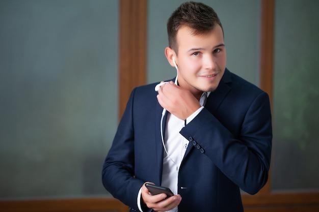 Il giovane operaio bello utilizza un telefono nell'ufficio della società