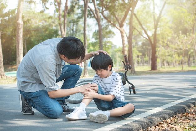 Il giovane padre asiatico di papà calma il figlio caduto dalla bicicletta e si infortuna al ginocchio e alla gamba mentre ha il fine settimana nel parco pubblico, l'incidente può accadere ovunque e ogni volta.