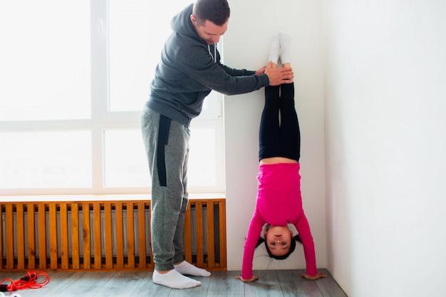 Il giovane padre e la sua piccola figlia sveglia hanno allenamento a casa. push-up verticale. ragazzo carino è in piedi sulle mani. indossano abiti sportivi e hanno esercizi vicino alla finestra nella stanza
