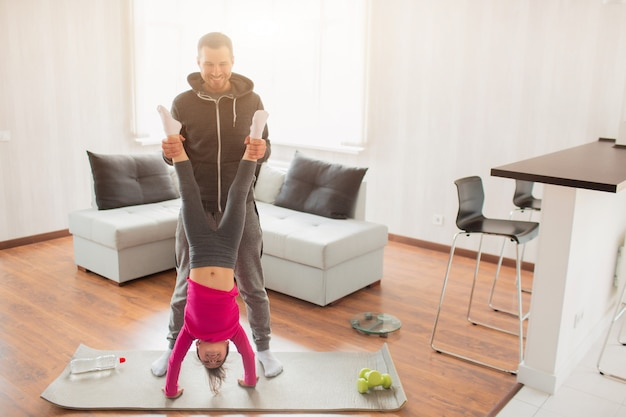 Il giovane padre e la sua piccola figlia sveglia hanno allenamento a casa. push-up verticale. ragazzo carino è in piedi sulle mani. si indossano in abbigliamento sportivo e hanno esercizi