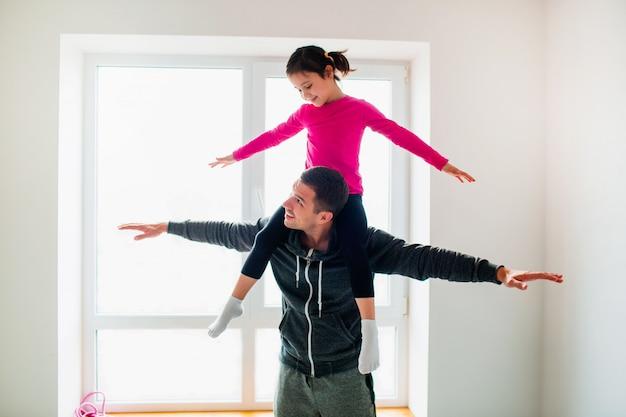 Il giovane padre e la sua piccola figlia sveglia hanno allenamento a casa. simpatico bambino e papà si sta allenando al coperto. il piccolo modello femminile dai capelli scuri in abiti sportivi ha esercizi vicino alla finestra nella stanza