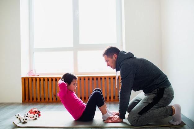 Il giovane padre e la sua piccola figlia sveglia hanno allenamento dell'abs a casa. simpatico bambino e papà si sta allenando su una stuoia al coperto. il piccolo modello femminile dai capelli scuri in abiti sportivi ha esercizi vicino alla finestra nella stanza